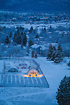 The Missoula, Montana valley in winter with a greenhouse lit up before dawn