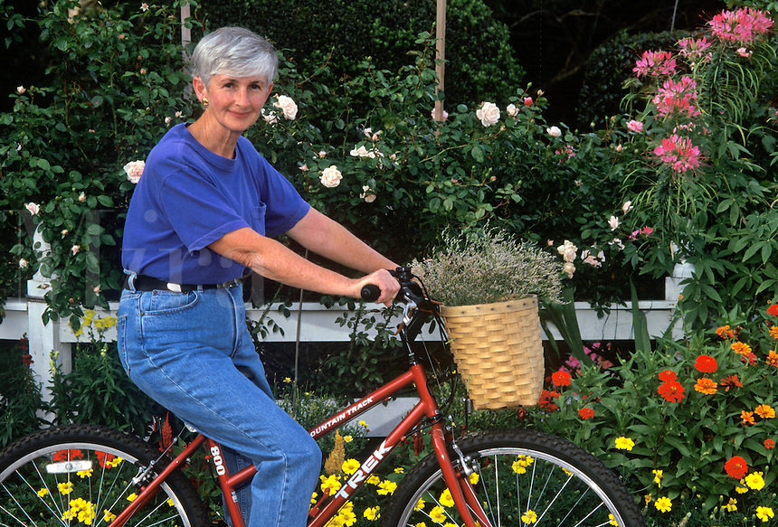 Senior woman on bicycle by flower garden.