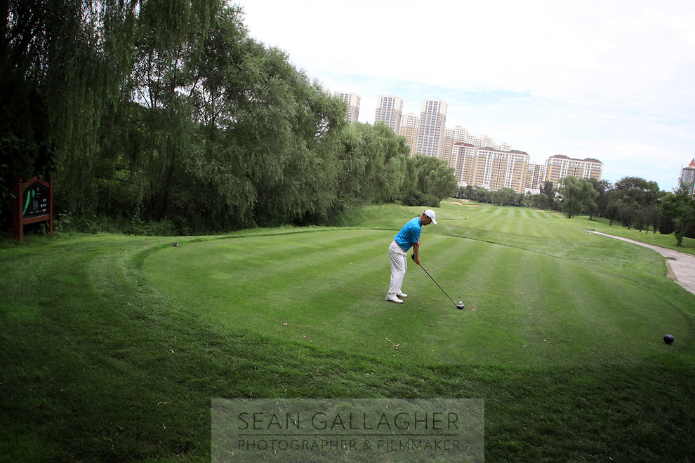 CHINA. A golfer tees off at the Huatang International Golf Club in Beijing. 2009