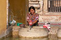Antigua, Guatemala.  Woman Doing Laundry at the Public Pila, or Washing Place.