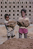 Children work at brick manufactuer in India - Child labor as seen around the world between 1979 and 1980 - Photographer Jean Pierre Laffont, touched by the suffering of child workers, chronicled their plight in 12 countries over the course of one year.  Laffont was awarded The World Press Award and Madeline Ross Award among many others for his work.