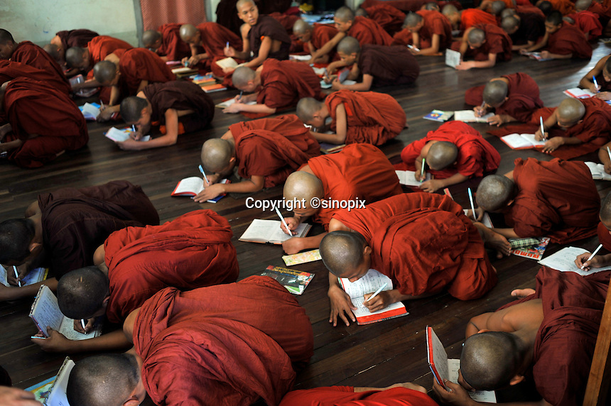"""Monks learn prayers in a monastery, Mandalay, Burma November 08.  Monks in this largely Buddhist country have to beg from villagers in order to feed themselves and in this city the government hand-outs stopped after the """"saffron revolution"""" of October 2007.<br /> <br /> Photo by Richard Jones"""