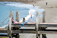 WEATHER PICTURE WALES A couple relax on the old wooden jetty on the beach as others paddle in the water. People enjoy the sunshine in Aberystwyth, Wales, UK. Thursday 23 June 2016