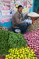 India, Dehradun.  Man Selling Potatoes, Onions, Oranges, Peppers, Ginger, and Garlic, while listening to music on earphones.