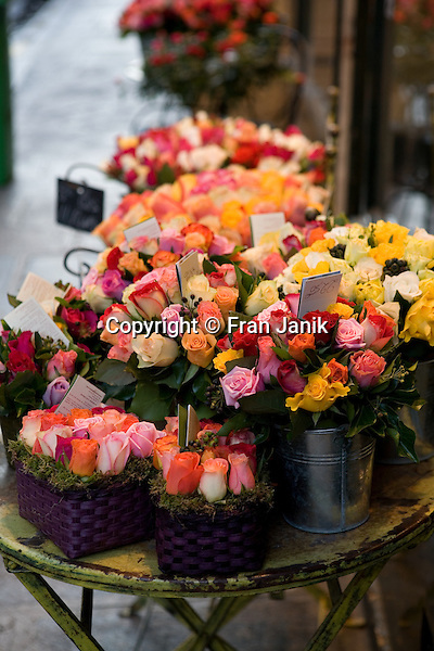 "Roses are captured artfully displayed in front of the small shop, ""au nom de la rose"",  in Paris France"