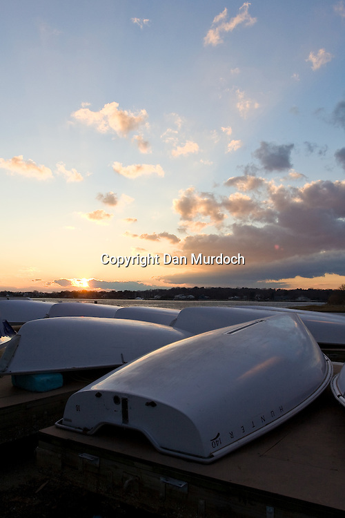 sunset over stored sailboats