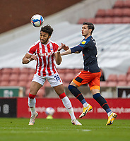 20th February 2021; Bet365 Stadium, Stoke, Staffordshire, England; English Football League Championship Football, Stoke City versus Luton Town; Jacob Brown of Stoke City heads the ball away from Potts of Luton