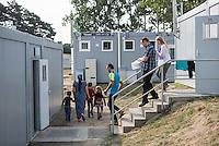 Zentrale Auslaenderbehoerde und BAMF-Aussenstelle in Eisenhuettenstadt.<br /> Bundesinnenminister Thomas de Maiziere und brandeburgs Ministerpraesident Dietmar Woidke besuchten am Donnerstag den 13. August 2015 die Zentrale Auslaenderbehoerde und BAMF-Aussenstelle in Eisenhuettenstadt. Sie liessen sich von Mitarbeitern die Situation in der Einrichtung zeigen und erklaeren, sprachen mit Fluechtlingen und besichtigten das auf dem Gelaende befindliche Abschiebegefaengnis.<br /> Der Besuch des Bundesinnenministers und des Ministerpraesidenten wurde von etwa 40 Journalisten begleitet.<br /> Im Bild: Fluechtlinge werden nach ihrer Ankunft auf dem Gelaende von Mitarbeitern der Auslaenderbehoerde begleitet.<br /> 13.8.2015, Eisenhuettenstadt/Brandenburg<br /> Copyright: Christian-Ditsch.de<br /> [Inhaltsveraendernde Manipulation des Fotos nur nach ausdruecklicher Genehmigung des Fotografen. Vereinbarungen ueber Abtretung von Persoenlichkeitsrechten/Model Release der abgebildeten Person/Personen liegen nicht vor. NO MODEL RELEASE! Nur fuer Redaktionelle Zwecke. Don't publish without copyright Christian-Ditsch.de, Veroeffentlichung nur mit Fotografennennung, sowie gegen Honorar, MwSt. und Beleg. Konto: I N G - D i B a, IBAN DE58500105175400192269, BIC INGDDEFFXXX, Kontakt: post@christian-ditsch.de<br /> Bei der Bearbeitung der Dateiinformationen darf die Urheberkennzeichnung in den EXIF- und  IPTC-Daten nicht entfernt werden, diese sind in digitalen Medien nach §95c UrhG rechtlich geschuetzt. Der Urhebervermerk wird gemaess §13 UrhG verlangt.]