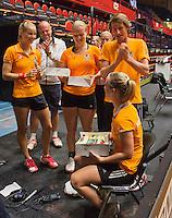 The Netherlands, Den Bosch, 16.04.2014. Fed Cup Netherlands-Japan, practice, Richel Hogenkamp receives a birthday cake from Arantxa Rus (L) (NED) coach Raymond Knaap, Kiki Bertens (NED) and captain Paul Haarhuis  (NED)<br /> Photo:Tennisimages/Henk Koster
