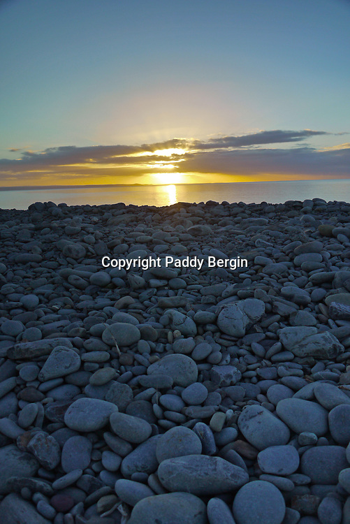 Sunset over pebble beach sones.<br /> <br /> Stock Photo by Paddy Bergin
