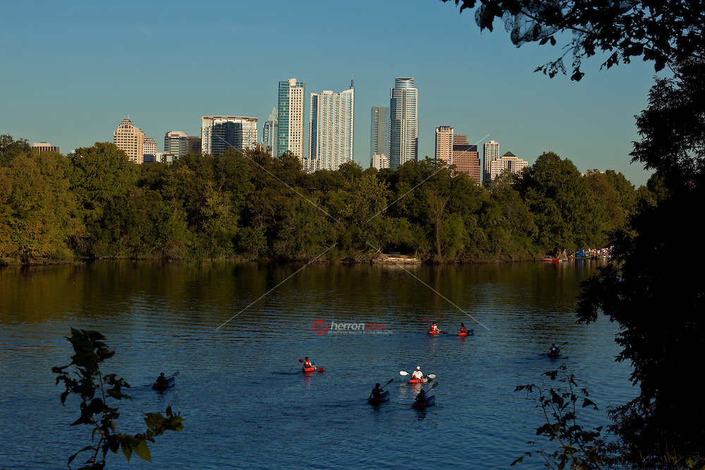 Water Enthusiasts in kayaks and canoes explore Town Lake.
