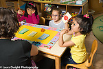 Education Preschool 4-5 year olds girls playing board game female teacher going over the rules