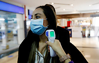 BOGOTA, COLOMBIA - JULY 03, 2020: An employee of a Beauty Care Center, takes a temperature of a co-worker in Bogota on July 3, 2020. During the Covid-19 pandemic, 180,000 workers are affected by the economic stagnation, resulting in an overall loss of $500 million dollars. (Photo by Leonardo Munoz/VIEWpress via Getty Images)