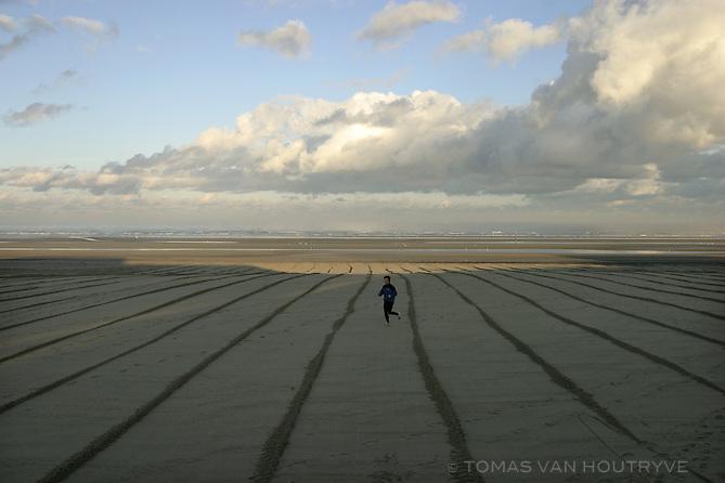 A jogger runs along groomed sand on the beach in Oostduinkerke, Belgium on 3 December, 2004.<br />