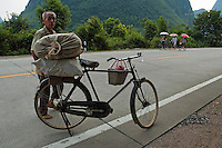 Man standing by his fully loaded bicycle on a country road, Yangshuo, Guangxi, China.