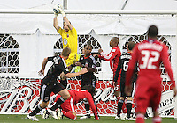 Troy Perkins #23 of D.C. United pulls in the ball over a fallen Wilman Conde #22 of the Chicago Fire during an MLS match on April 17 2010, at RFK Stadium in Washington D.C. Fire won the match 2-0.