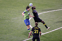COLUMBUS, OH - DECEMBER 12: Gustav Svensson #4 of the Seattle Sounders FC and Gyasi Zardes #11 of the Columbus Crew challenge for a header during a game between Seattle Sounders FC and Columbus Crew at MAPFRE Stadium on December 12, 2020 in Columbus, Ohio.