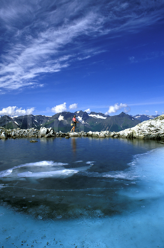 Hiker stands at an alpine tarn on Mt. Alice, Chugach National Forest, Alaska.  MR