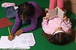 public school elementary grades Grade 2 two girls side by side on floor one reading and the other writing