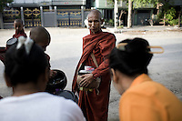 A group of novice monks, led by an older monk, collect food on their early morning alms round.