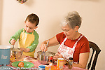 3 year old boy cooking baking activity with grandmother  modeling imitation stirring his own bowl as grandmother stirs hers