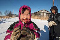 """Danny-Girl"" and her big brother Corey from Zackar Levi School in Lower Kalskag put on their gloves to go skiiing with their Skiku coaches. Skiku is a non-profit organization with the mission of creating a sustainable Nordic ski program in communities throughout Alaska. Volunteer coaches travel to villages each spring to instruct youngsters and distribute donated equipment with the goal of establishing ski programs at rural schools.  Photo by James R. Evans"