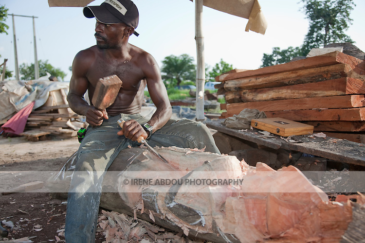 A man makes wood carvings in Nigeria's capital city of Abuja.