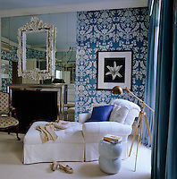 The bedroom walls are covered in blue and white St. Antoine wallpaper by Farrow & Ball