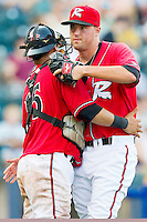 Closer Heath Hembree #35 of the Richmond Flying Squirrels gets a hug from catcher Eliezer Zambrano #15 after getting the final out against the Harrisburg Senators in game one of a double-header at The Diamond on July 22, 2011 in Richmond, Virginia.  The Squirrels defeated the Senators 3-1.   (Brian Westerholt / Four Seam Images)