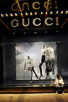 A lovely angelic girl sits outside a Gucci Shop in Hong Kong. Gucci, one of the world's leading high-quality luxury brands that.manufacturers its all products in Italy.  In 2009, Gucci generated 2,266 million Euro in revenues and finished the year with 283 directly operated stores.  Gucci and other luxury brands have been investing heavily in Asia, especially China which they seen as their highest potential growth area..\