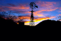 A windmill in silhouette at sunset.