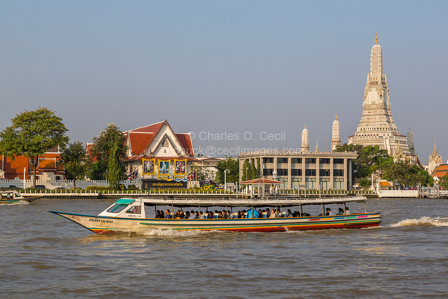 Bangkok, Thailand.  Morning Water Taxi on the Chao Phraya River Takes Commuters to Work.  Wat Arun Temple in the Background.