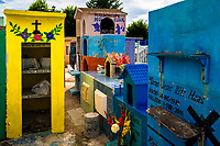 """Colorful niches and above-ground tombs, adorned with flowers, are seen during the bone cleansing ritual at the cemetery in Pomuch, Mexico, 26 October 2019. Every year on the Day of the Dead, people of Pomuch, a small Mayan community in the south of Mexico, visit the cemetery to take part in a pre-Hispanic tradition of cleaning of bones of their departed relatives (""""Limpia de huesos""""). People who die in Pomuch are firstly buried for three years in an above-ground tomb then the dried-up bodies are taken out, bones are separated, wrapped in a decorated cloth, put into a wooden crate, and placed on display among flowers for veneration."""