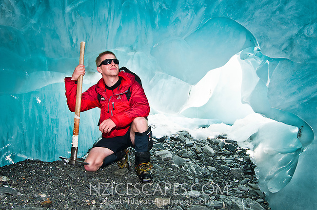 Glacier guide admiring an ice cave on Franz Josef Glacier - Westland National Park, West Coast, New Zealand