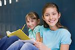 USA, Illinois, Metamora, Portrait of two girls (8-9) sitting at lockers in school corridor and doing homework