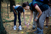 Jennifer Klein (right) shows a small plant to Aileen Merino, 11, as she and other sixth grade students from Roger Williams Middle School in Providence, Rhode Island, walk along a trail at the Powder Mill Ledges Wildlife Refuge in Smithfield, Rhode Island, on Oct. 20, 2011. The students are part of the EcoExplorer program run by the Providence After School Alliance, which helps to kids in learning environments outside of school time. The students make a weekly visit to the refuge, operated by the Rhode Island Audubon Society, to learn about nature and ecology.<br /> <br /> <br /> M. Scott Brauer for Education Week