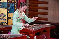 Yangzhou, Jiangsu, China.  Young Woman Playing the Guzheng, Slender West Lake Park.