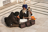 Amritsar, Punjab, India. The Golden Temple - Harmandir Sahib. Two Sikh musicians sitting cross-legged on the marble floor, one playing a Sarangi using a bow.