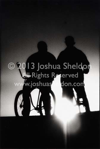 Sihlouetted Boys on Bicycles at sunset<br />
