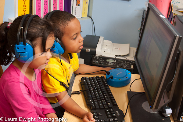 Education Preschool 3-4 year olds boy and girl using computer to play learning bame in classroom wearing headphones