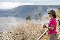 A woman looks at Halema'uma'u Crater and steam vents at Hawai'i Volcanoes National Park, Big Island.