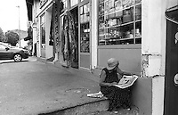 Belgrado, una donna legge il giornale seduta su dei gradini in strada --- Belgrade, a woman reads the newspaper while sitting on the steps in the street