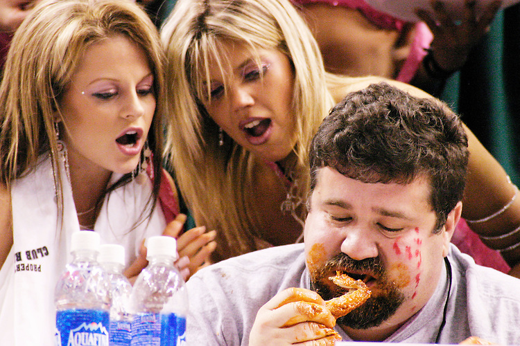 """Mo Green and his Wingettes at the 13th annual Wing Bowl, held in Philadelphia on February 4, 2005 at the Wachovia Center.<br /> <br /> The Wing Bowl is a competitive eating event in which eaters try and down the most hot wings in 30 total minutes in front of a crowd of 10,000 plus people.  The real show however is all around the eaters, from the various scantily clad women, known as """"Wingettes"""", that make up competitors' entourages to the behavior of the fans themselves."""