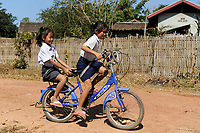 LAOS Province Vientiane, village Tham , two girls coming from school by bicycle / Kinder kommen mit dem Fahrrad von der Schule