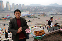 CHINA. Sichuan Province. Chongqing. A man selling food next to The Yangtze River which is at its lowest level in 150 years as a result of a country-wide drought. Chongqing is a city of over 3,000,000 people, famed for being the capital of China between 1938 and 1946 during World War II. It is situated on the banks of the Yangtze river, China's longest river and the third longest in the world. Originating in Tibet, the river flows for 3,964 miles (6,380km) through central China into the East China Sea at Shanghai.  2008.