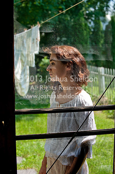 Young woman through screen door