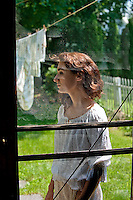 Young woman through screen door