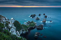 Dawn with brooding skies at Nugget Point lighthouse with rocky islets, Catlins, East Coast, Southland, New Zealand, NZ
