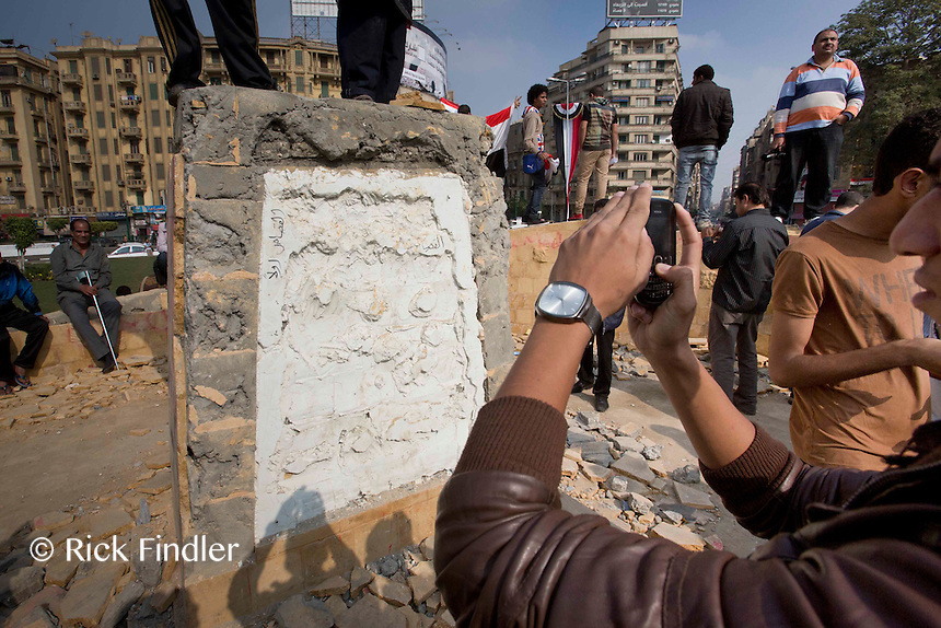 19.11.13 Locals take pictures of a recently demolished memorial in Tahir Square. The memorial, which comemorates hundreds of people killed in clashes five months ago, was completed less than 24 hours before this picture.