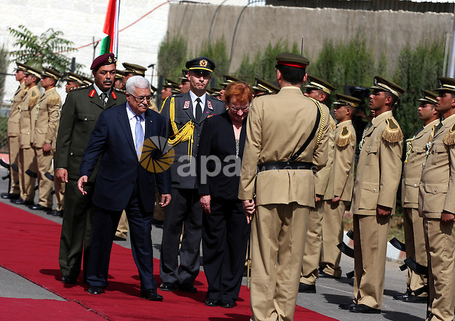 Palestinian President Mahmoud Abbas and Finland's President Tarja Halonen walk past an honour guard before their meeting in the West Bank city of Ramallah on October 14, 2010 . Photo by Issam Rimawi